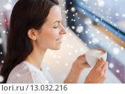 Купить «smiling young woman drinking coffee at cafe», фото № 13032216, снято 20 декабря 2014 г. (c) Syda Productions / Фотобанк Лори