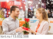 Купить «happy couple with present and flowers in mall», фото № 13032508, снято 10 ноября 2014 г. (c) Syda Productions / Фотобанк Лори