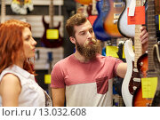 Купить «couple of musicians with guitar at music store», фото № 13032608, снято 11 декабря 2014 г. (c) Syda Productions / Фотобанк Лори