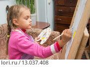 Купить «Девочка рисует красками рисунок на мольберте в мастерской художника», фото № 13037408, снято 13 октября 2015 г. (c) Иванов Алексей / Фотобанк Лори