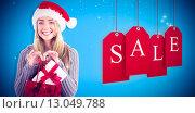 Купить «Composite image of festive blonde holding christmas gift and bag», фото № 13049788, снято 10 июля 2020 г. (c) Wavebreak Media / Фотобанк Лори