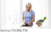 Купить «smiling young woman chopping eggplant at home», видеоролик № 13050776, снято 1 мая 2015 г. (c) Syda Productions / Фотобанк Лори
