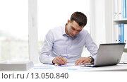 Купить «busy businessman with laptop and papers in office», видеоролик № 13050840, снято 8 июля 2015 г. (c) Syda Productions / Фотобанк Лори