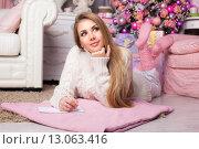 Купить «Задумчивая красивая молодая женщина подписывает рождественскую открытку, лежа на полу дома», фото № 13063416, снято 31 октября 2015 г. (c) Швайгерт Екатерина / Фотобанк Лори