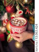 Купить «Женские руки держат чашку с кофе и зефиром на фоне рождественской елки», фото № 13063424, снято 31 октября 2015 г. (c) Швайгерт Екатерина / Фотобанк Лори