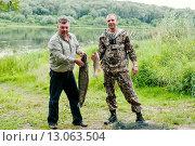 Купить «Радостные рыбаки держат пойманную рыбу в руках на фоне реки», эксклюзивное фото № 13063504, снято 24 июля 2015 г. (c) Игорь Низов / Фотобанк Лори