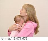 Купить «Молодая женщина обнимает плачущего младенца», фото № 13071676, снято 19 ноября 2014 г. (c) Ирина Борсученко / Фотобанк Лори