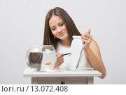 Девушка просит у золотой рыбки желания записанный в блокноте. Стоковое фото, фотограф Иванов Алексей / Фотобанк Лори