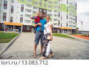 Купить «Счастливая семья стоит  во дворе нового дома», фото № 13083712, снято 25 июня 2015 г. (c) Алексей Маринченко / Фотобанк Лори