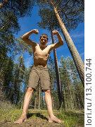 Купить «Молодой человек стоит демонстрирует бицепсы в лесу», фото № 13100744, снято 13 июня 2015 г. (c) Алексей Маринченко / Фотобанк Лори