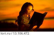 Купить «Charming woman reading shining book», фото № 13106472, снято 4 июля 2014 г. (c) Ingram Publishing / Фотобанк Лори