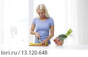 Купить «smiling young woman chopping pepper at home», видеоролик № 13120648, снято 2 мая 2015 г. (c) Syda Productions / Фотобанк Лори