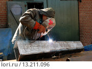 Купить «A welder works on a piece of metal on a Rotterdam shipyard.», фото № 13211096, снято 13 октября 2018 г. (c) age Fotostock / Фотобанк Лори