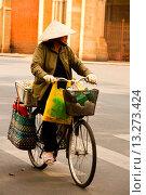 Купить «Woman riding bicycle in Ho Chi Minh City, Vietnam», фото № 13273424, снято 12 июля 2020 г. (c) age Fotostock / Фотобанк Лори