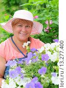 Купить «Улыбающаяся женщина ухаживает за цветами в саду», эксклюзивное фото № 13277400, снято 9 июня 2013 г. (c) Юрий Морозов / Фотобанк Лори