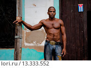 Купить «A young Cuban man of an athletic, muscular look stands half naked on the street of Santiago de Cuba, Cuba, 29 July 2008  About 50 years after the national...», фото № 13333552, снято 29 июля 2007 г. (c) age Fotostock / Фотобанк Лори