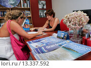 Купить «A girl in a travel agency, Spain», фото № 13337592, снято 13 августа 2010 г. (c) age Fotostock / Фотобанк Лори