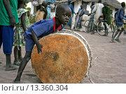 Купить «Mvolo, South Sudan: February 9, 2006. A young boy plays with a drum half his size in the small town of Mvolo, South Sudan.», фото № 13360304, снято 9 февраля 2006 г. (c) age Fotostock / Фотобанк Лори