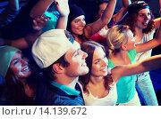 Купить «smiling friends at concert in club», фото № 14139672, снято 20 октября 2014 г. (c) Syda Productions / Фотобанк Лори