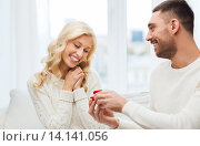 Купить «happy man giving engagement ring to woman at home», фото № 14141056, снято 8 октября 2015 г. (c) Syda Productions / Фотобанк Лори