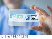 Купить «close up of woman with transparent smartphone», фото № 14141848, снято 13 августа 2015 г. (c) Syda Productions / Фотобанк Лори