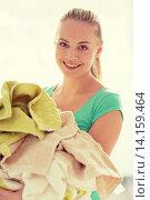 Купить «happy woman carrying clothes to laundry at home», фото № 14159464, снято 25 января 2015 г. (c) Syda Productions / Фотобанк Лори