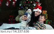 Купить «Мама с сыном делают новогоднее селфи», видеоролик № 14337636, снято 2 декабря 2015 г. (c) Сергей Мнацаканов / Фотобанк Лори