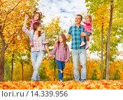 Купить «Многодетная семья гуляет в парке осенью, взявшись за руки», фото № 14339956, снято 27 сентября 2015 г. (c) Сергей Новиков / Фотобанк Лори
