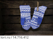 Купить «Жаккардовые женские рукавицы висят на веревке на деревянном фоне», фото № 14716412, снято 5 декабря 2015 г. (c) Наталья Осипова / Фотобанк Лори