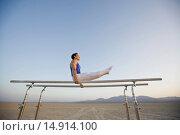 Купить «Gymnast Performing on Parallel Bars in the Desert», фото № 14914100, снято 26 июля 2006 г. (c) age Fotostock / Фотобанк Лори