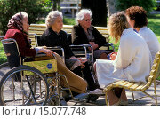 elderly care nurses and old women in wheelchairs sitting together outside. Стоковое фото, фотограф McPHOTO / age Fotostock / Фотобанк Лори
