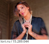 Купить «Portrait of a 30 year old brunette woman wearing a negligee and a pearl necklace looking directly at the camera on the porch of an old house.», фото № 15289044, снято 21 ноября 2014 г. (c) age Fotostock / Фотобанк Лори