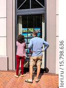 Купить «Couple looking at a window display of homes for sale outside a real estate brokers office in Sarasota FL.», фото № 15798636, снято 21 февраля 2015 г. (c) age Fotostock / Фотобанк Лори