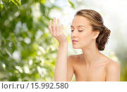 Купить «woman smelling perfume from wrist of her hand», фото № 15992580, снято 31 октября 2015 г. (c) Syda Productions / Фотобанк Лори