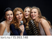Купить «happy young women with microphone singing karaoke», фото № 15993148, снято 21 ноября 2015 г. (c) Syda Productions / Фотобанк Лори