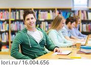 Купить «happy student boy reading books in library», фото № 16004656, снято 6 марта 2015 г. (c) Syda Productions / Фотобанк Лори