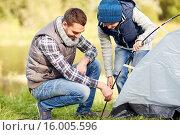 Купить «happy father and son setting up tent outdoors», фото № 16005596, снято 27 сентября 2015 г. (c) Syda Productions / Фотобанк Лори