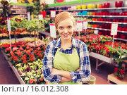 Купить «happy woman with flowers in greenhouse», фото № 16012308, снято 25 февраля 2015 г. (c) Syda Productions / Фотобанк Лори