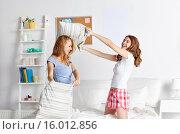 Купить «happy teen girl friends fighting pillows at home», фото № 16012856, снято 14 ноября 2015 г. (c) Syda Productions / Фотобанк Лори