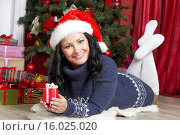 Девушка в новогоднем колпаке с получила подарок. Стоковое фото, фотограф Светлана Микитанская / Фотобанк Лори