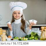 Купить «Little girl holding soft cheese in packs at kitchen», фото № 16172604, снято 25 января 2020 г. (c) Яков Филимонов / Фотобанк Лори