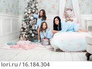 Семья в одинаковой одежде  в спальне перед елкой украшают ее и веселятся. Стоковое фото, фотограф Nataliya Pogodina / Фотобанк Лори