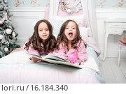 Две девочке на кровати читают книжку, рядом елка. Стоковое фото, фотограф Nataliya Pogodina / Фотобанк Лори