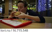 Купить «Подросток жадно ест гамбургер», видеоролик № 16715548, снято 30 ноября 2015 г. (c) Валентин Беспалов / Фотобанк Лори