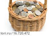 Купить «Плетеная корзинка, наполненная монетами различных стран», фото № 16720472, снято 30 января 2014 г. (c) Евгений Ткачёв / Фотобанк Лори