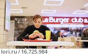 Купить «Молодая женщина ест гамбургер», видеоролик № 16725984, снято 6 декабря 2015 г. (c) Валентин Беспалов / Фотобанк Лори