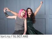 Подруги веселятся на фоне стены. Стоковое фото, фотограф Nataliya Pogodina / Фотобанк Лори