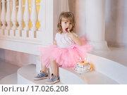 Девочка на лестнице пробует именинный торт. Стоковое фото, фотограф Tanya Ischenko / Фотобанк Лори