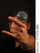 """Купить «Мужчина с микрофоном в руке показывает жест """"коза"""" на черном фоне», фото № 17070080, снято 16 декабря 2015 г. (c) Anton Eine / Фотобанк Лори"""