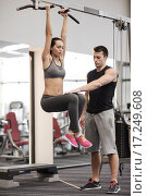 Купить «young woman with trainer doing leg raises in gym», фото № 17249608, снято 30 ноября 2014 г. (c) Syda Productions / Фотобанк Лори